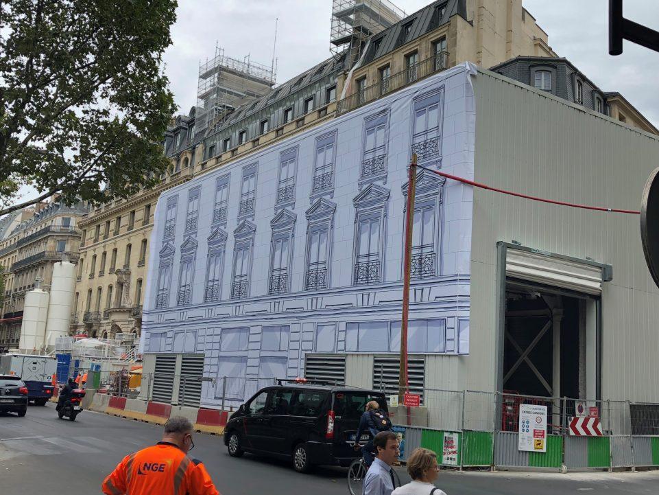 Une façade d'immeuble recouverte d'une fresque en noir et blanc de fenêtres le temps des travaux