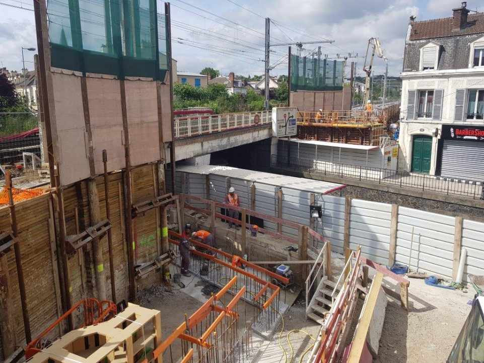 Image de chantier en plein jour sous un pont, des ouvriers sont à l'oeuvre