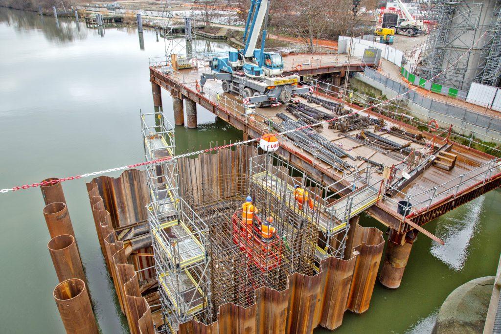 Sur la photo, les piles sur lesquelles le pont-rail et la passerelle douce s'appuieront sont en cours de construction, dans la Seine.