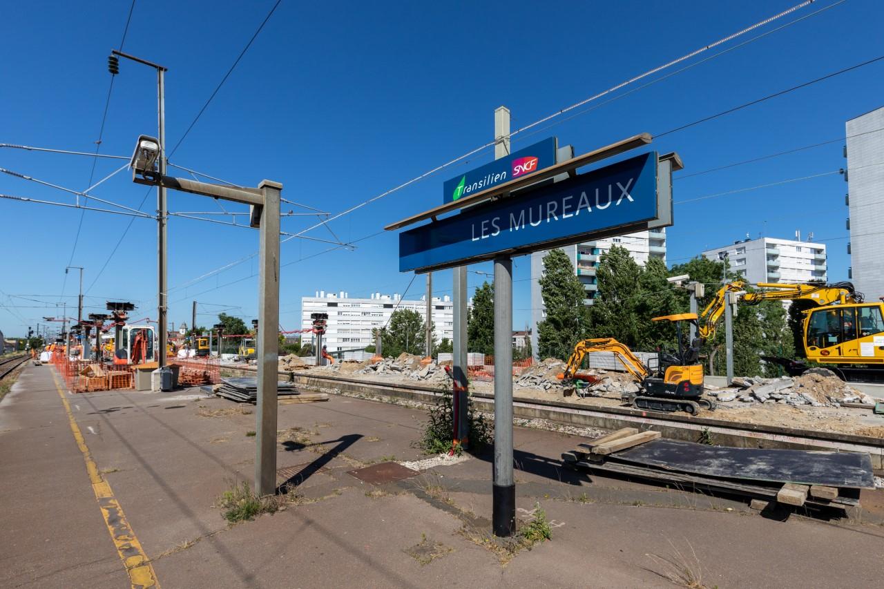 """Quai de la gare Les Mureaux, panneau d'affichage indiquant le nom de l'arrêt """"Les Mureaux"""" en bleu, en face d'habitations"""
