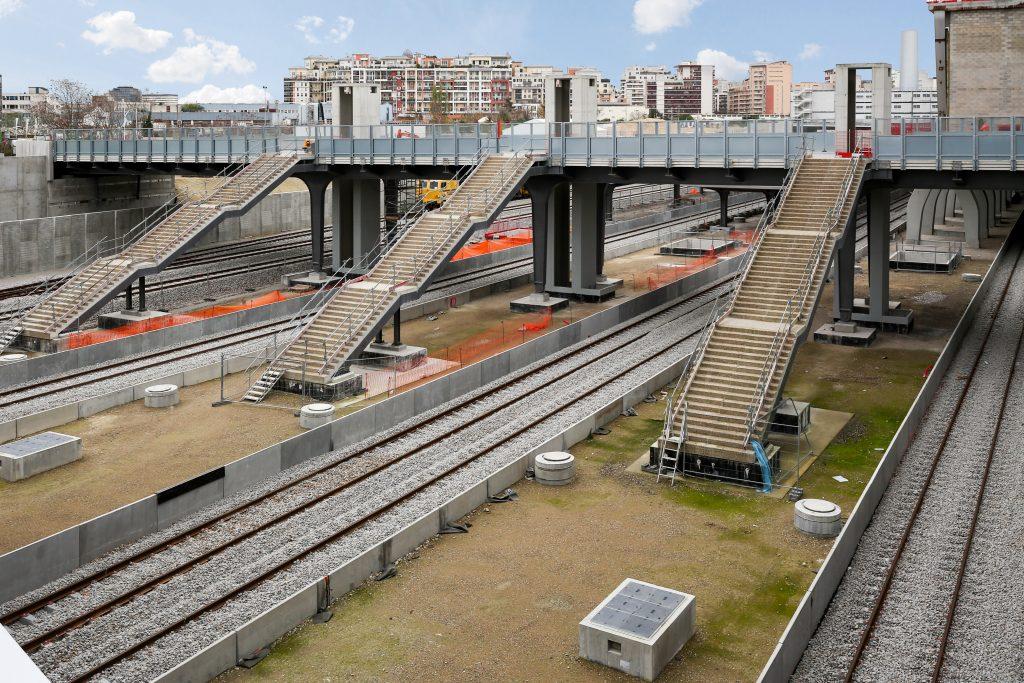 Vue de la gare de Nanterre avec les voies, les quais, la passerelle, les escaliers et les structures des futurs ascenseurs